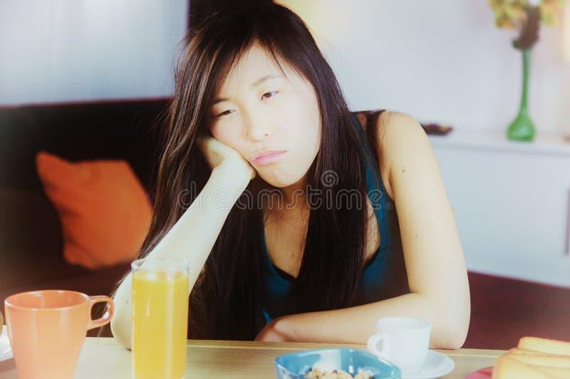 Unhappy sad Chinese woman tired at home closeup stock photo
