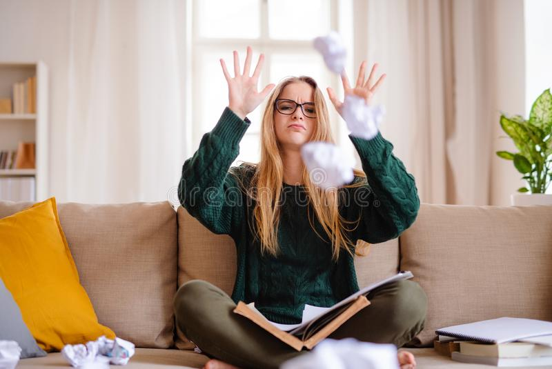 An unhappy female student sitting on sofa, studying. An unhappy, sad and frustrated female student sitting on sofa, studying royalty free stock images