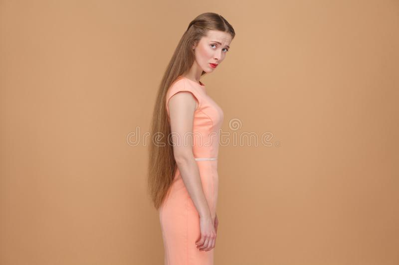 Unhappy sad woman with long brown hair looking at camera. Emotional cute, beautiful woman with makeup and long hair in pink dress. indoor, studio shot stock images