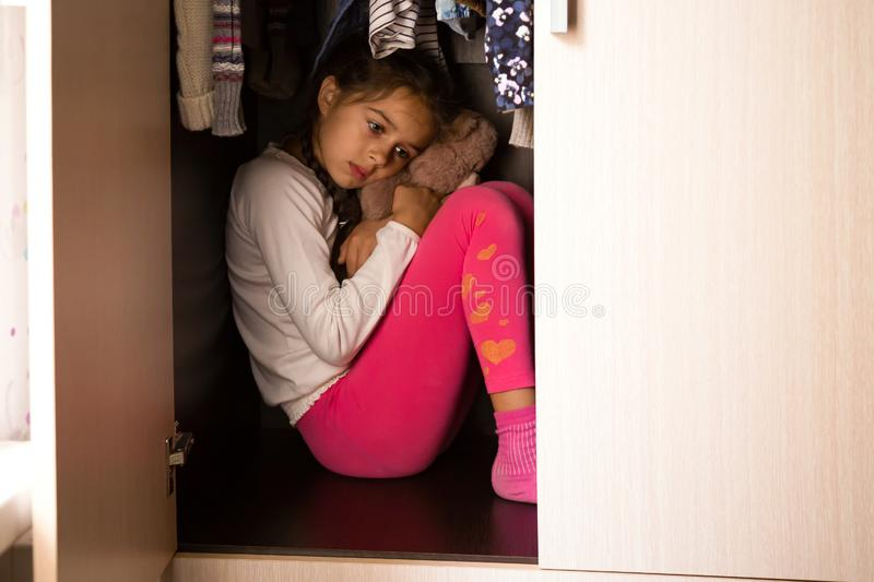 Unhappy and scared child hiding in the wardrobe and sitting there with Teddy in her hands. Domestic violence and abused concept. Unhappy and scared child hiding stock photos