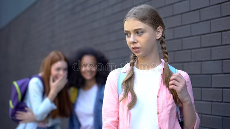 Unhappy schoolgirl standing front of laughing cruel pupils, college mocking. Stock photo stock photos