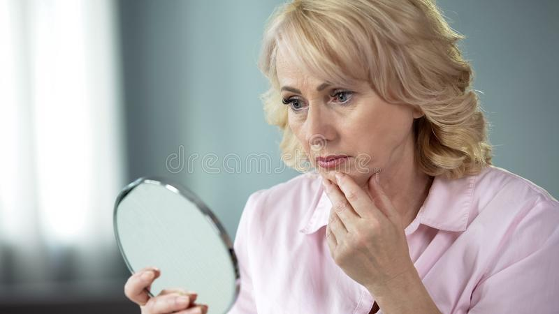 Unhappy senior female looking at sagging skin face in mirror, old age appearance stock image
