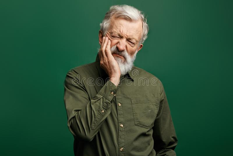 Unhappy senior man suffers from toothache stock photos
