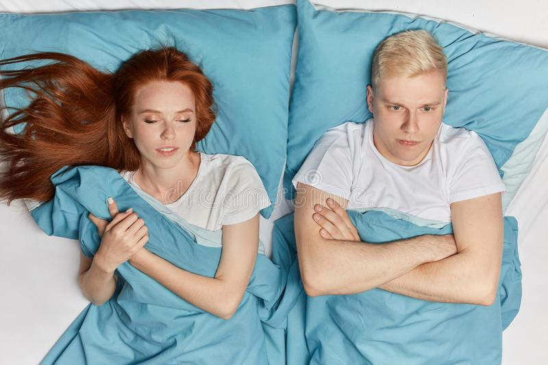 Unhappy serious man lying with crossed arms cannot fall asleep. Unhappy serious men lying with crossed arms cannot fall asleep men is thinking about family royalty free stock images