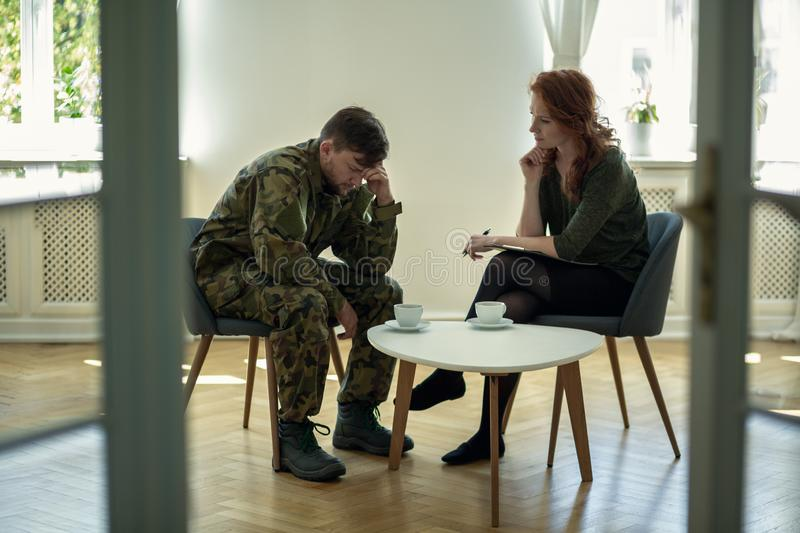 Unhappy soldier in green uniform and psychotherapist during consultation in the office royalty free stock image