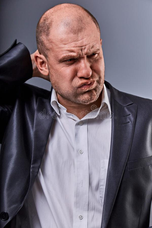 Unhappy stressed bald angry business man holding the head with very bad emotions in office suit on grey studio background. Closeup stock photos