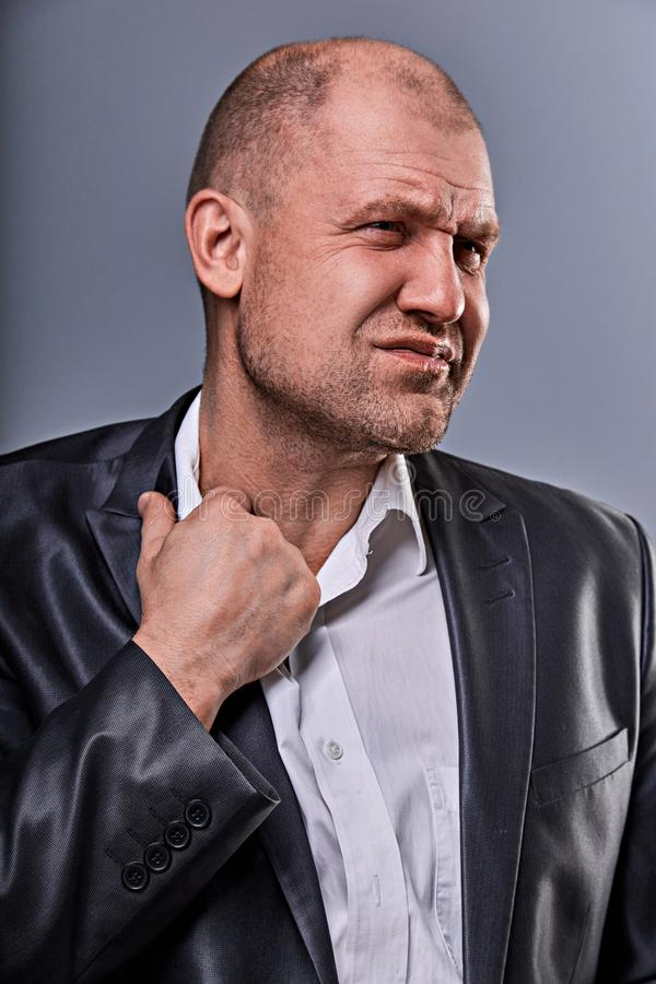 Unhappy stressed bald angry business man pulling the shirt collar with very bad emotions in office suit on grey studio background royalty free stock photos
