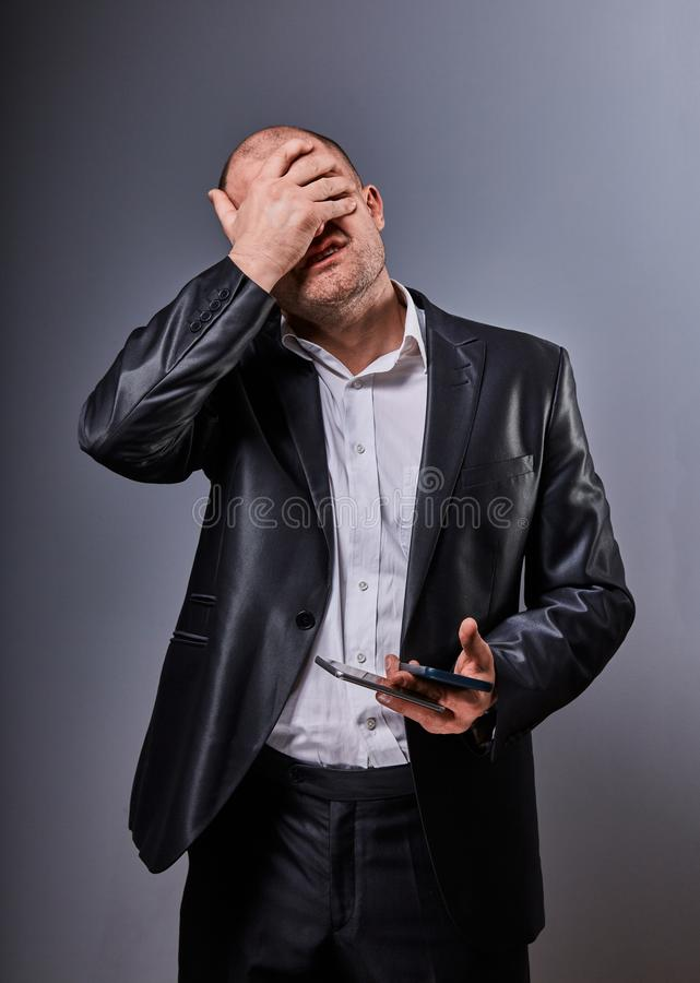 Unhappy stressed depressed business man holding in hand two mobile phones and covering the face the palm in office suit on grey stock photo