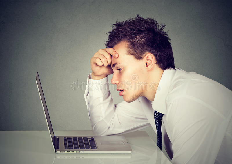 Unhappy stressed sad man sitting at desk in front of his laptop. Unhappy stressed man sitting at desk in front of his laptop royalty free stock photography