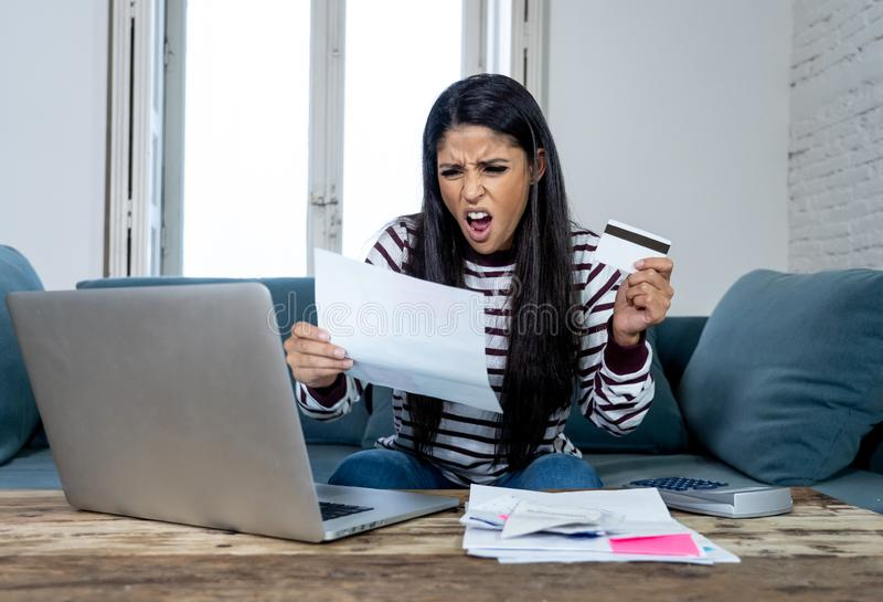 Unhappy stressed young female angry with credit card bill calculating home finance and paying bills stock photography