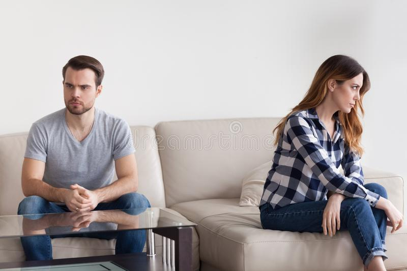 Unhappy stubborn married couple feel angry frustrated sitting on couch. Avoid ignore talk after fight, irritated annoyed husband and wife having disagreement royalty free stock image