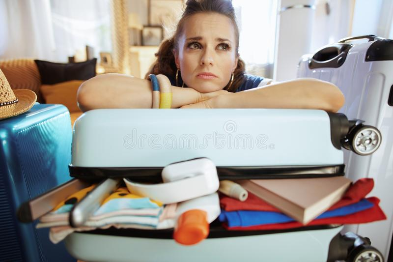 Unhappy stylish woman relaxing on over packed suitcase stock photography