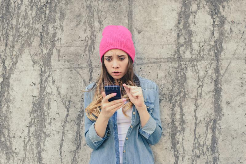 Unhappy surprised sad jealous woman reading sms on her boyfriend`s mobile phone. Cell cellphone mobile phone telephone smartphone stock photo