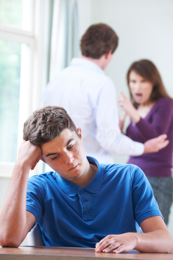 Unhappy Teenage Boy With Parents Arguing In Background royalty free stock image