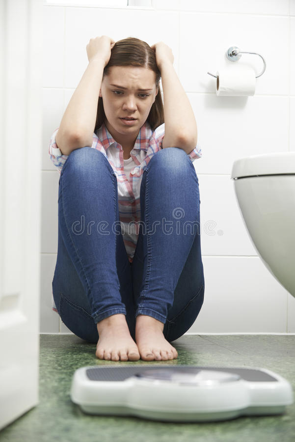 Unhappy Teenage Girl Sitting On Floor Looking At Bathroom Scales stock photography