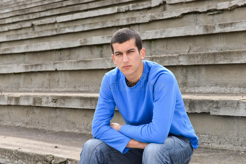 Unhappy teenage student sitting outside on stadium steps stock photos