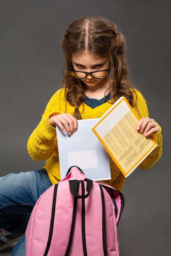 Unhappy tired schoolgirl in eyeglasses puting the exercise books in pink backpack on grey studio background in fashion style stock image