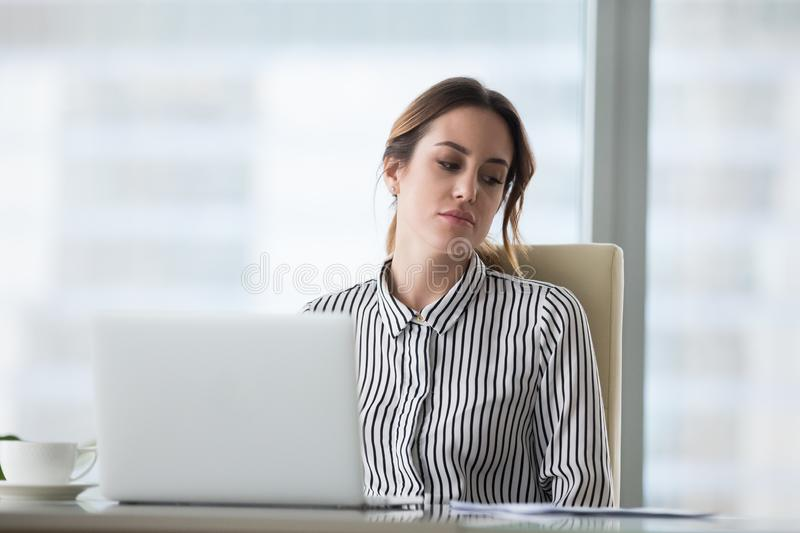 Unhappy tired young woman sitting at workplace. royalty free stock photo