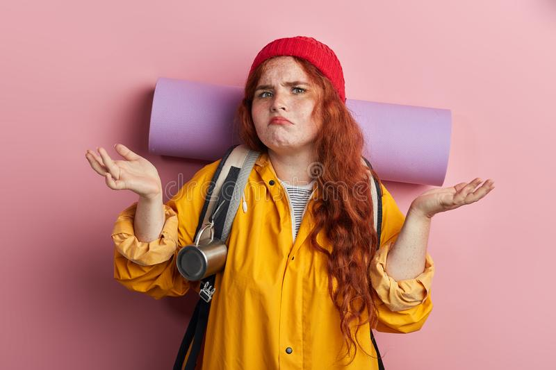 Unhappy woman with clueless and confused expression shrugging her shoulders. stock photography