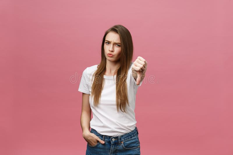 Unhappy woman giving thumbs down gesture looking with negative expression and disapproval. royalty free stock photography