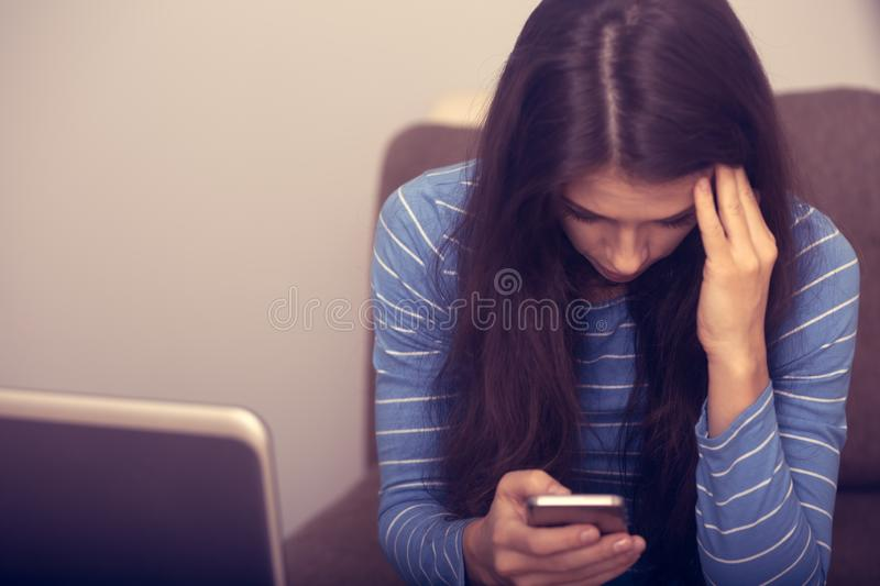Unhappy woman with headache sitting near the laptop and writing sms in mobile phone. Closeup portrait of business person on work royalty free stock photo