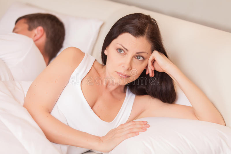Unhappy woman lying in bed stressed. Couple having problem while men sleeping royalty free stock photography