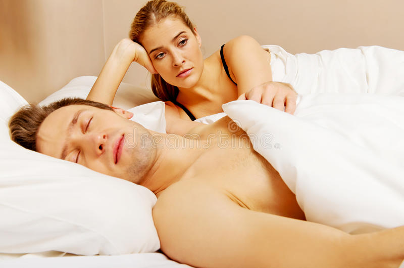 Unhappy woman lying in bed stressed when her husband sleeping stock photo