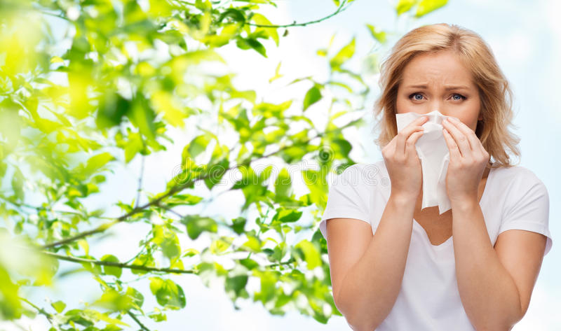 Unhappy woman with paper napkin blowing nose stock photography