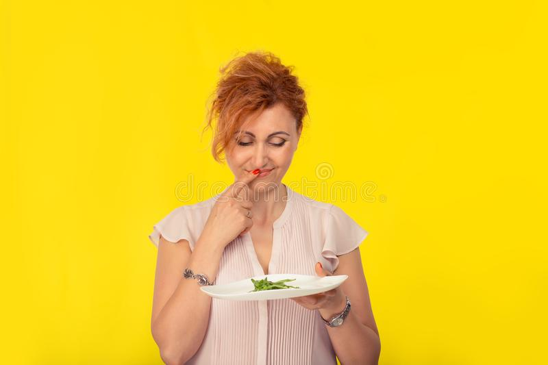 Unhappy woman with a plate of green salad stock images