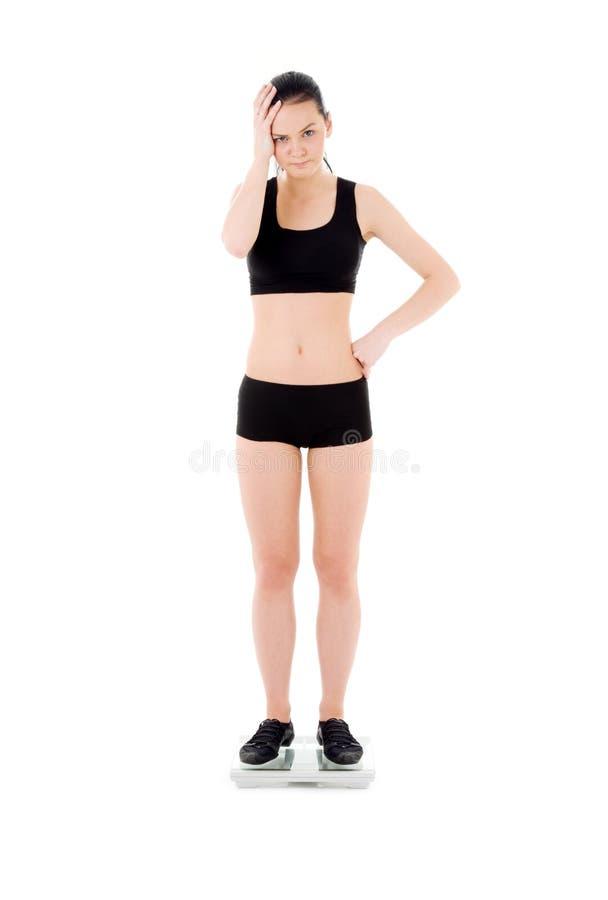 Unhappy woman on scales royalty free stock photos