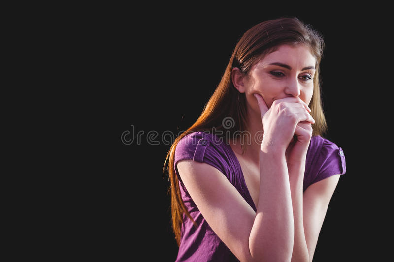 Unhappy woman thinking. On black background stock photography