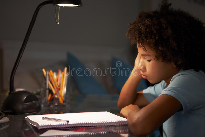 Unhappy Young Boy Studying At Desk In Bedroom In Evening stock photography