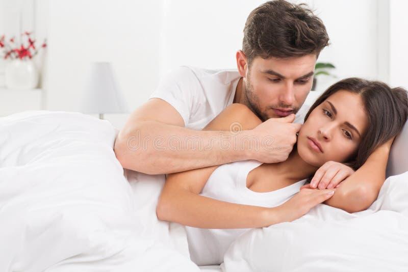 Unhappy young couple in bedroom stock photos