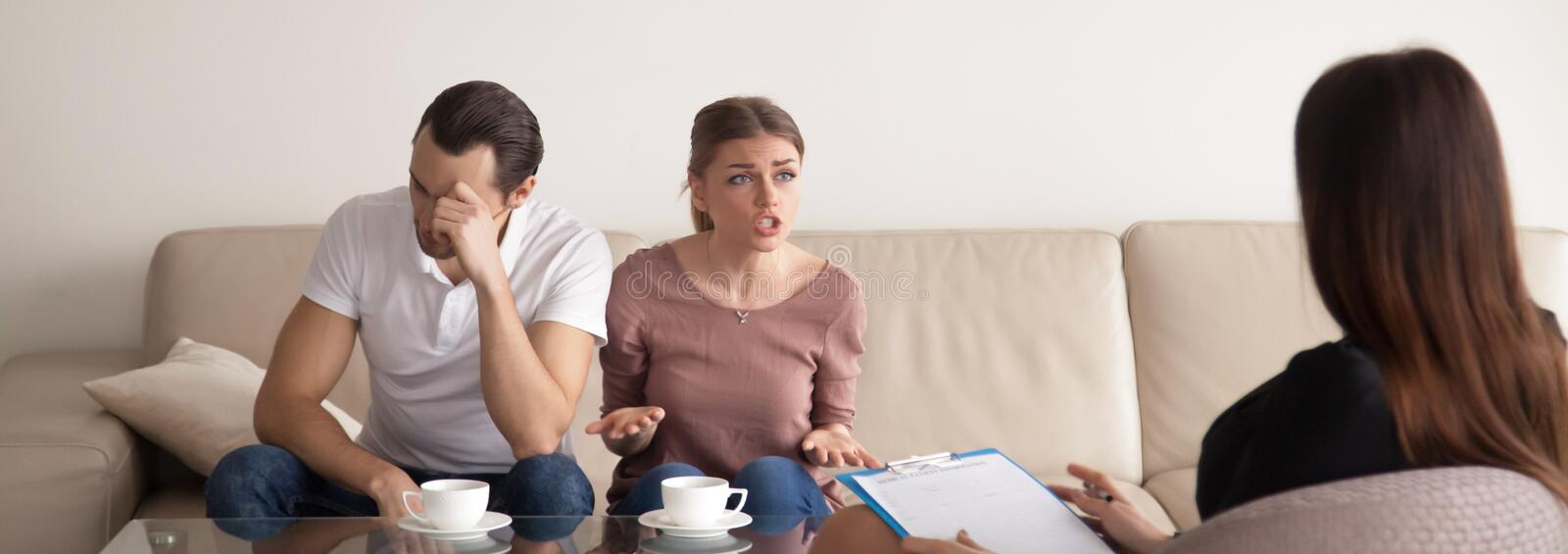 Unhappy young couple consulting family psychologist, arguing, ho. Unhappy young couple discussing with family psychologist problems in relationships, quarrelling royalty free stock images