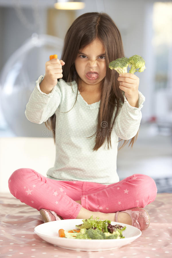 Unhappy Young Girl Rejecting Plate Of Fresh Vegetables stock photo
