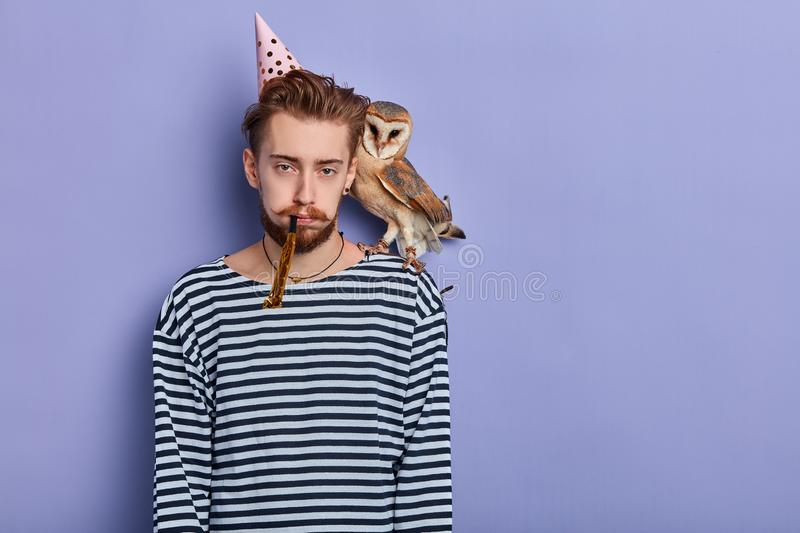 Unhappy young man with an owl in his shoulder is disappointed. Because nobody came to celebrate his anniversary, . People and celebration. isolated blue stock image