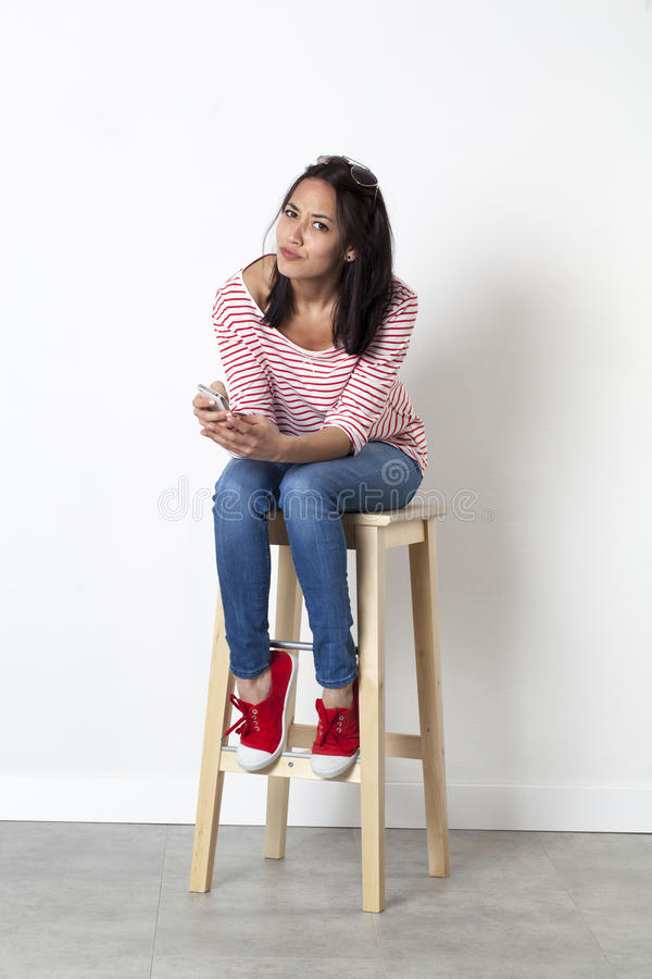 Unhappy young multiethnic female student dialing on mobile phone stock photos