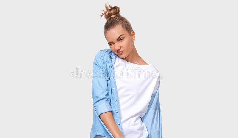Unhappy young woman frowning the face, wearing casual outfit with hair bun. Puzzled female posing over white studio wall. People. And emotions concept royalty free stock photo