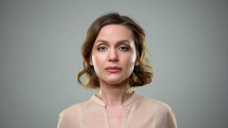 Unhappy young woman on grey background, female loneliness, breakup depression royalty free stock images