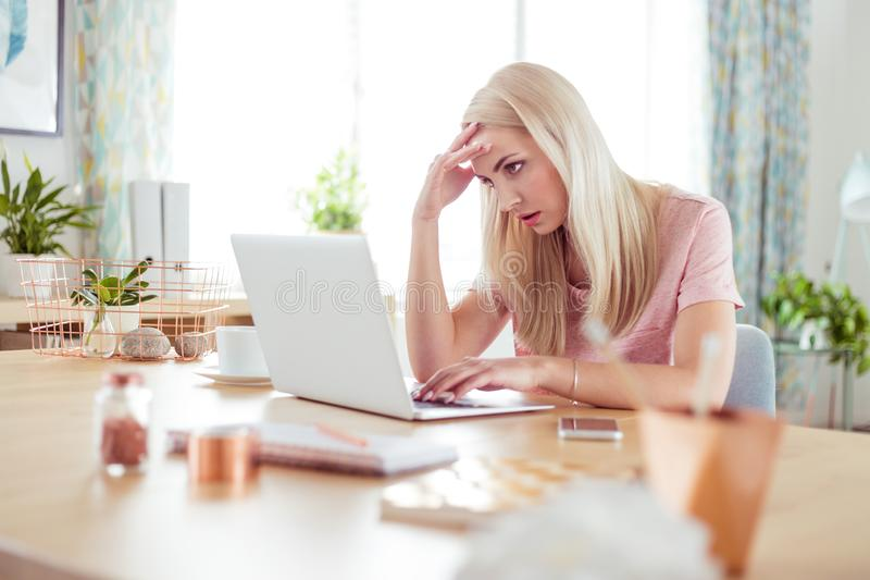 Worried young woman working on laptop at home stock image