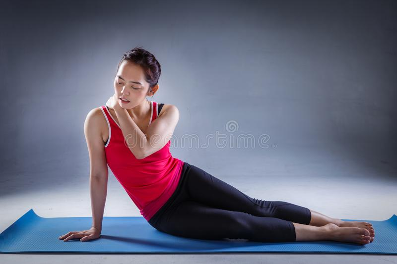 Unhappy young woman sitting on the mat, grabbing nape, unable to start yoga work out because of sport injury royalty free stock photos