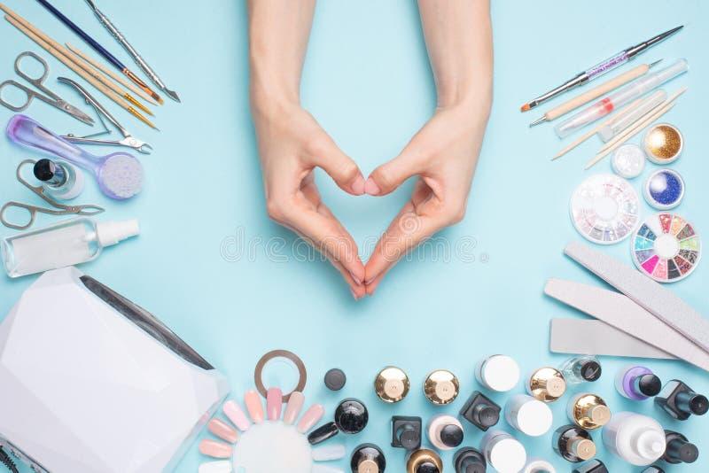 Unhas belamente preparadas sob a forma de um coração no desktop com as ferramentas para o tratamento de mãos Cuidado sobre o nort fotos de stock