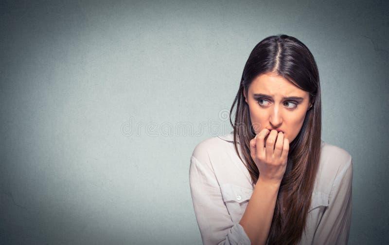 Unhas cortantes da mulher nervosa hesitante nova que imploram ou ansiosas foto de stock