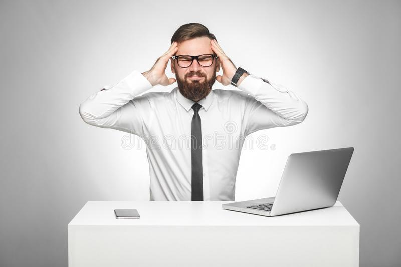 ?? unhealphy痛苦的年轻经理画象白色衬衫的和半正式礼服在办公室坐并且有强的头疼 免版税库存照片