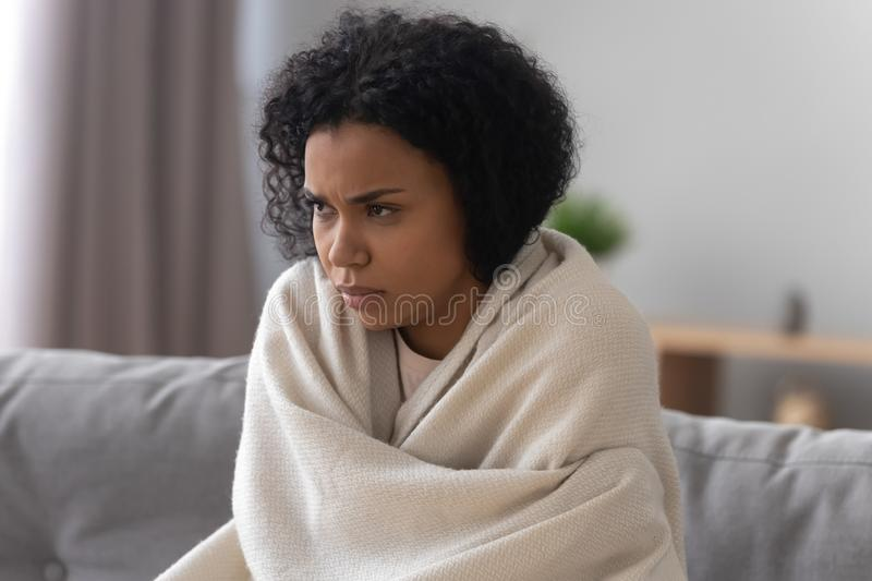 Unhealthy african American woman covered in blanket feel unwell stock photo