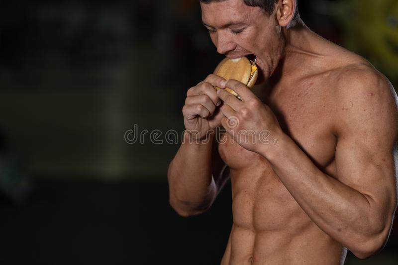 Unhealthy diet concept, athlete eats hamburger. Unhealthy diet concept, muscular male athlete eats hamburger. Bad dieting or sport, lifestyle choice stock image