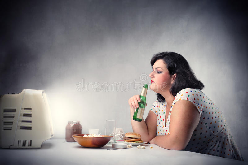 Unhealthy dinner. Fat woman sitting in front of a the television and drinking a bottle of beer royalty free stock photo