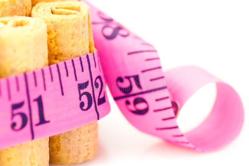 Unhealthy eating concept. Cakes rounded inch scale measuring tape. Shallow depth of field stock photos