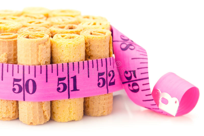 Unhealthy eating concept. Cakes rounded inch scale measuring tape. Shallow depth of field stock photo