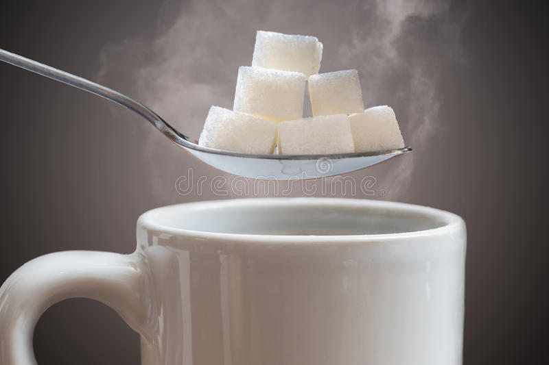 Unhealthy eating concept. Many sugar cubes above hot cup of tea or coffee royalty free stock photo